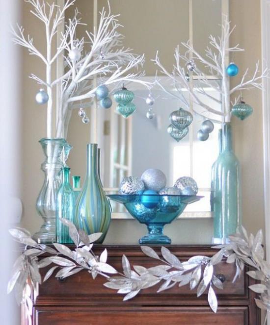 Blau und Silber Weihnachten und Silvester feiern Deko-Arrangement Vasen weiße Zweige Anhänger Girlande aus silbernen Blättern