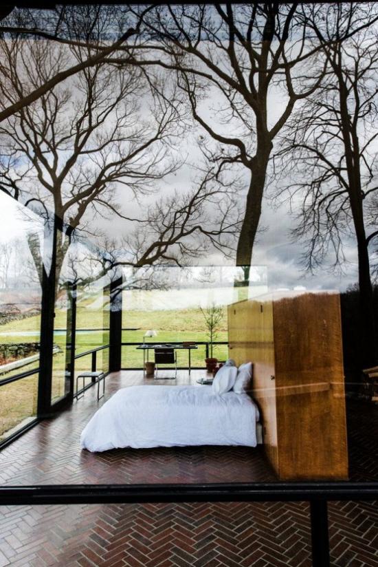Glaswände im Schlafzimmer draußen im Garten eins mit der Natur viel Grün hohe Bäume ringsherum