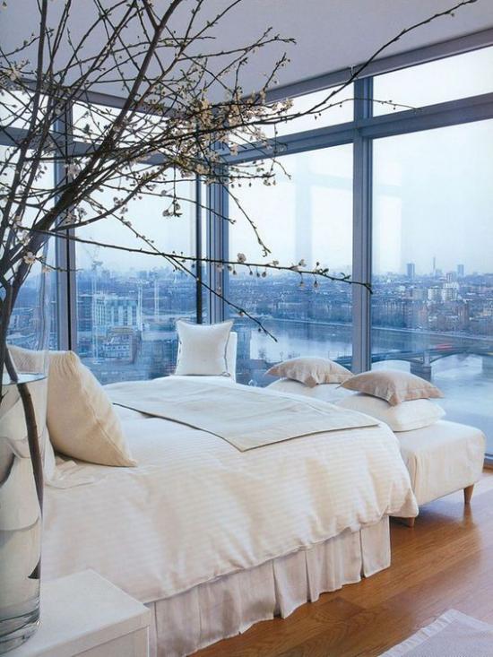 Glaswände im Schlafzimmer herrliche Aussicht Stadtpanorama Zweige in Vase neben dem Schlafbett
