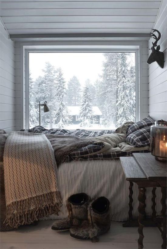 Glaswände im Schlafzimmer kleiner Schlafbereich Bett vor dem Fenster Winterlandschaft draußen