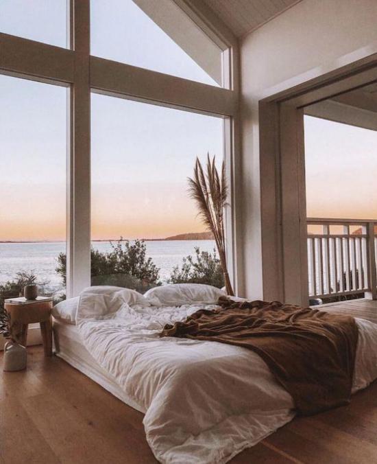 Glaswände im Schlafzimmer romantische Aussicht Meer Schlafbereich in warmen Farben