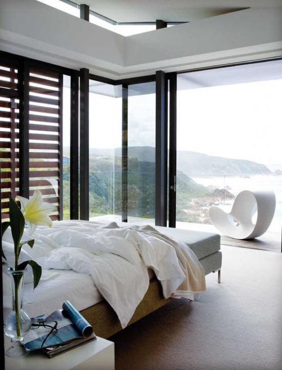 Glaswände im Schlafzimmer schickes Schlafzimmer an der der Küste Holzrollos Panoramablick