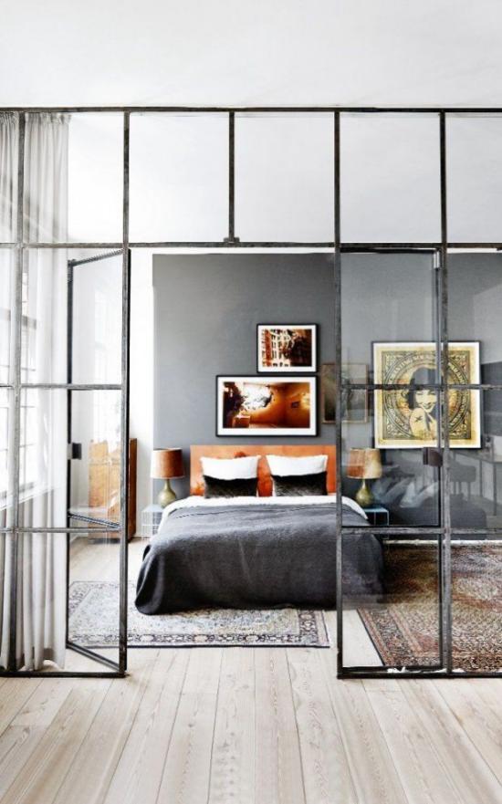 Glaswände im Schlafzimmer schwarzer Metallrahmen zwei bunte Teppiche interessante Wandbilder sehr einladend