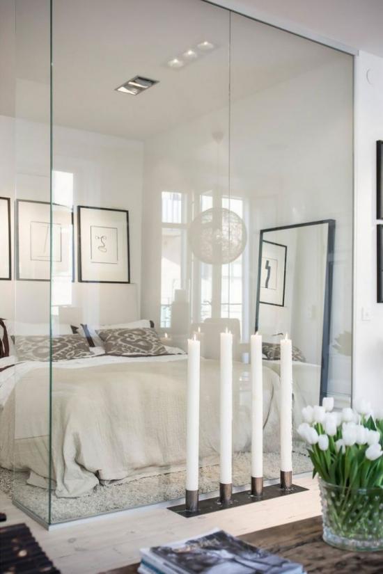 Glaswände im Schlafzimmer vier große weiße Kerzen künstliches Licht ausgefallene Raumgestaltung