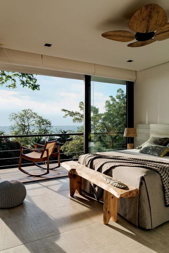 Glaswände im Schlafzimmer warme Brauntöne im Raum viel Grün draußen