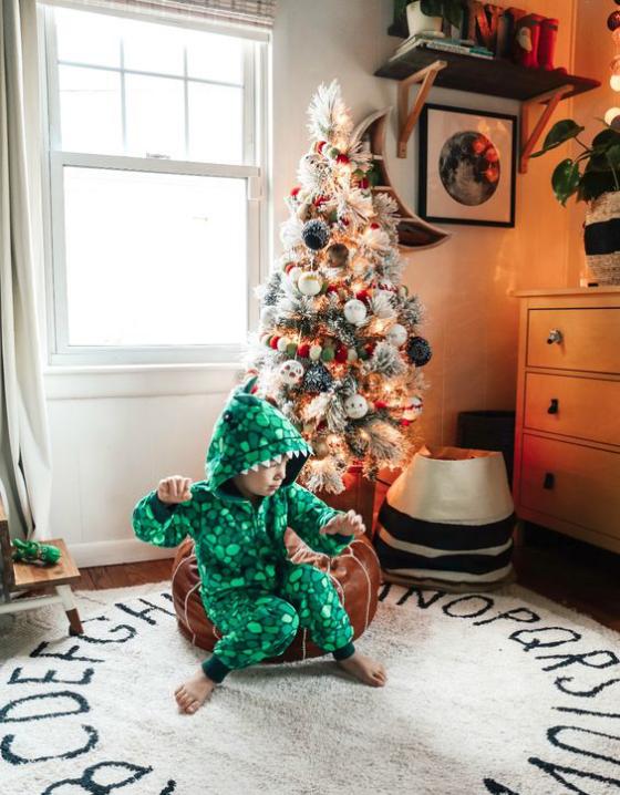 Kinderzimmer weihnachtlich dekorieren Spielparadies schön dekorierter Christbaum kleiner Junge vorne auf dem Teppich