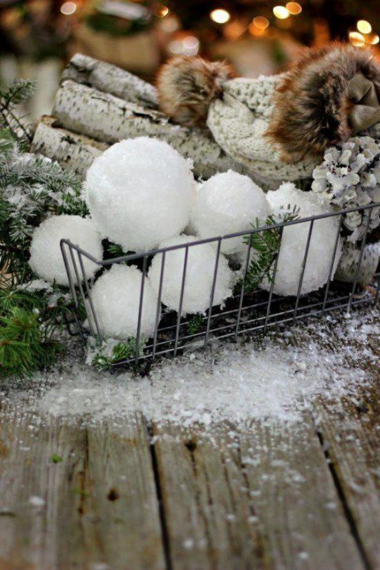 Schneebälle Winterdekoration mit Brennholz Tannengrün Mütze aus Wolle Zapfen im Gitter