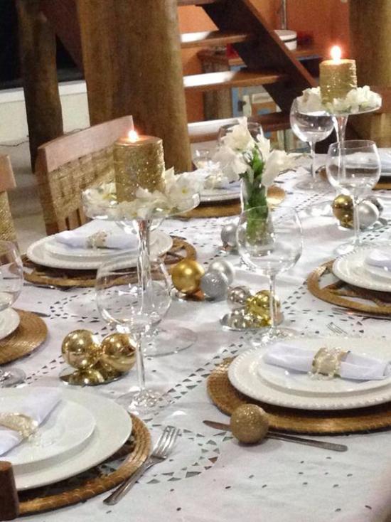 Silvester feiern zu Hause Gold-und Silberkugeln Kerzen weiße Blüten den festlich gedeckten Tisch zum Strahlen bringen
