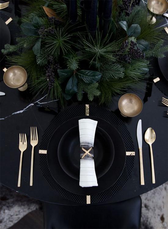 Silvester feiern zu Hause festlich gedeckter Tisch schwarze Tischdecke schwarzes Service goldglitzerndes Besteck etwas Grün in der Tischmitte