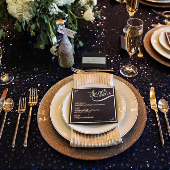 Silvester feiern zu Hause gedeckter Tisch schwarze Tischdecke Goldglitzer feines Besteck auch in Gold