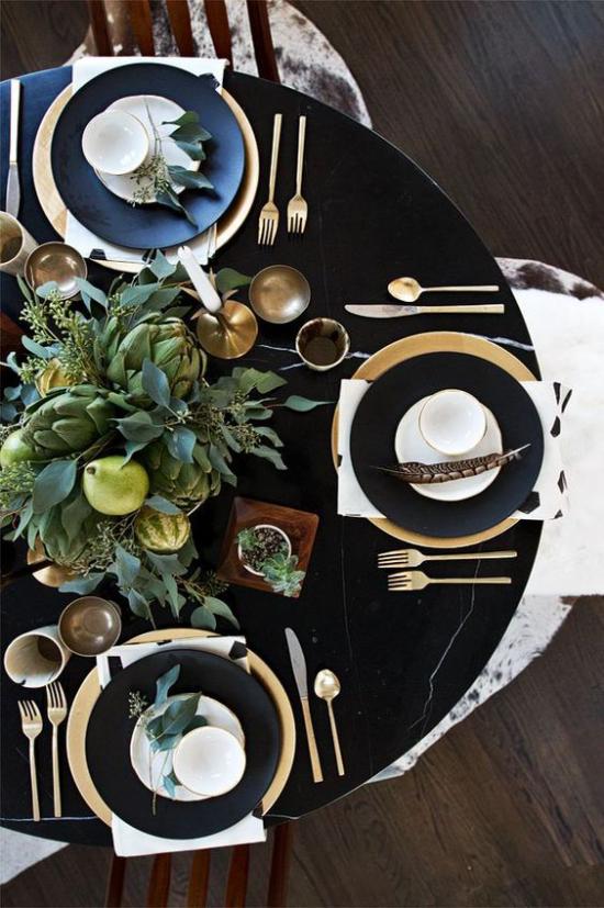 Silvester feiern zu Hause schön arrangierte Festtafel Service in Gold und Schwarz feines Besteck in der Tischmitte Vase mit grünen Zweigen