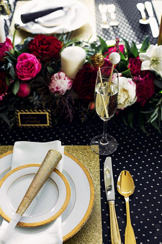 Silvester feiern zu Hause stilvolles Tischarrangement Schwarz Weiß Gold dunkelrote Blüten in der Mitte