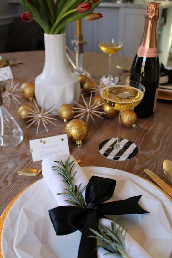 Silvester feiern zu Hause weiße Serviette schwarzes Band viele Goldglitzer Sektflasche Vase mit Tulpen
