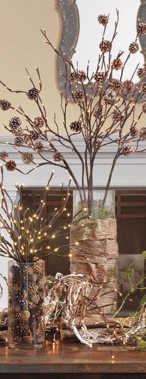 Tannenzapfen Winterdeko im Glasgefäß mit Lichtern an Zweigen befestigt in einer Vase arrangiert