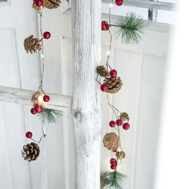 Tannenzapfen Winterdeko winterliche Lichterkette tolle Dekoidee rustikal an einer Holzleiter hängend