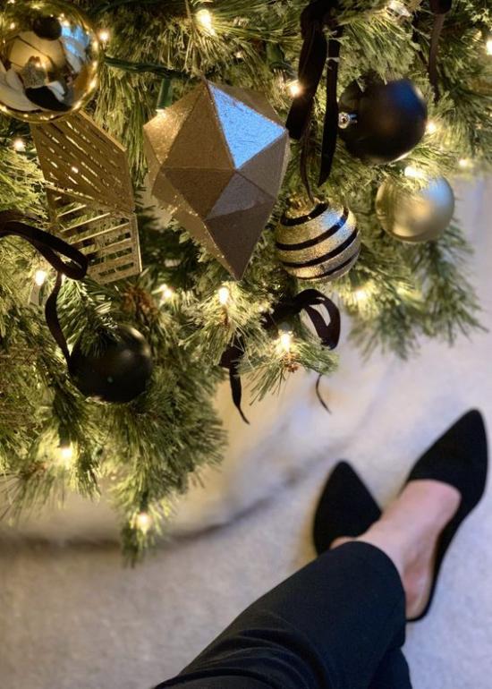 Weihnachtsdeko in Gold und Schwarz Christbaum goldgelbe und schwarze Kugeln weitere Ornamente Schleifen eine Frau daneben