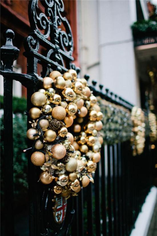 Weihnachtsdeko in Gold und Schwarz Kranz aus goldenen Weihnachtskugeln auf schwarzem Hintergrund Zaun