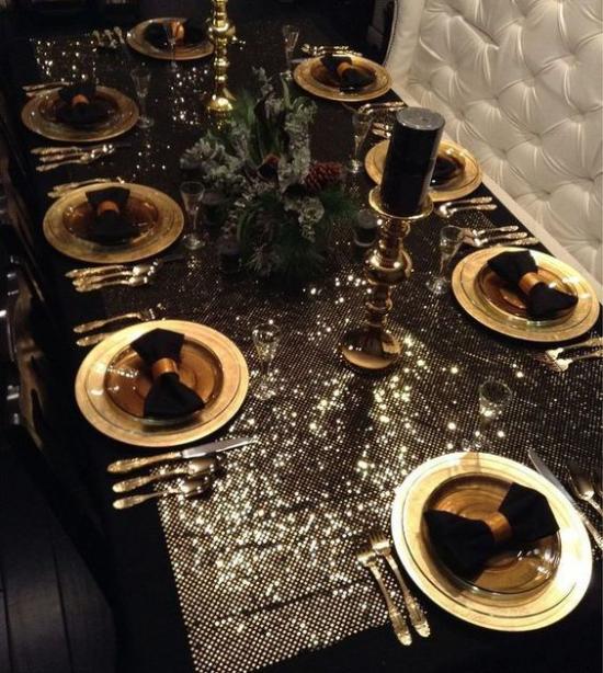 Weihnachtsdeko in Gold und Schwarz festlich gedeckter Esstisch sehr spektakulär glitzernde Tischdecke goldenes Geschirr schwarze Servietten