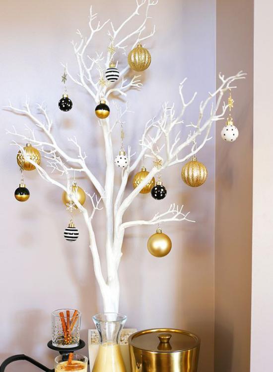 Weihnachtsdeko in Gold und Schwarz weiße Zweige goldgelbe Kugeln als Akzente wenig Schwarz
