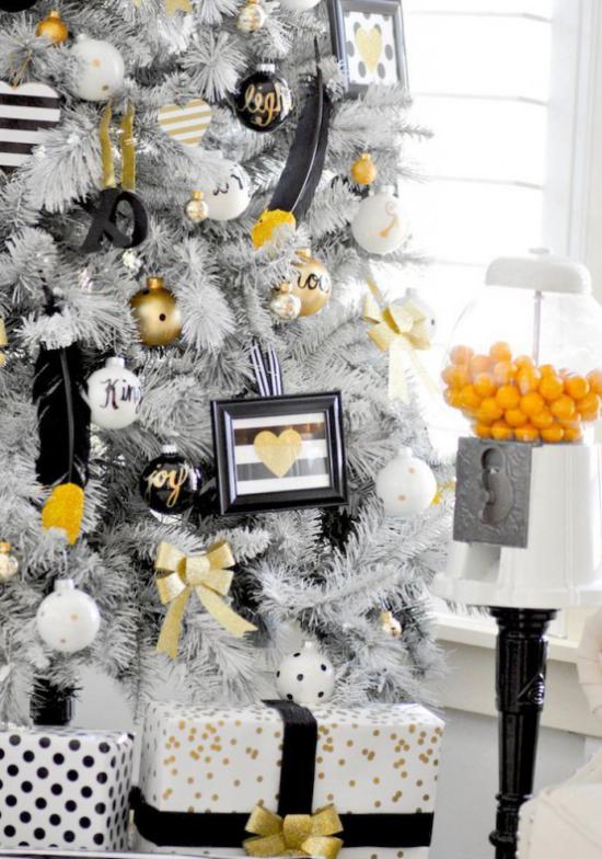 Weihnachtsdeko in Gold und Schwarz weißer Tannenbaum verpackte Geschenke darunter einzelne Akzente in Gold und Schwarz