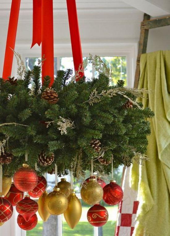 Weihnachtsdeko in Rot und Gold üppiger Weihnachtsschmuck hängt vom Kronleuchter viel Tannengrün Zapfen Anhänger