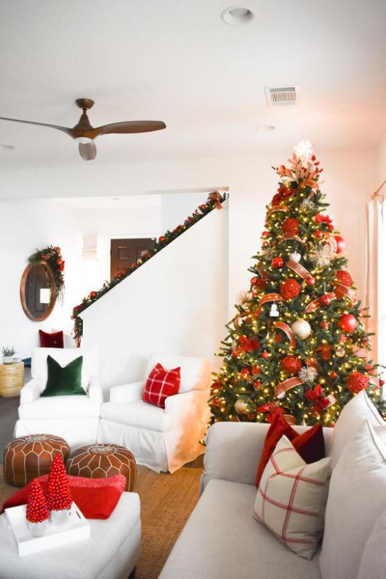 Weihnachtsdeko in Rot und Gold Christbaum üppig geschmückt Blickfang weißes Interieur