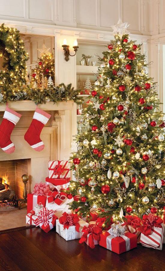 Weihnachtsdeko in Rot und Gold Weihnachtsbaum geschmückt neben dem Kamin Nikolausstiefel am Kaminsims zahlreiche Geschenke Lichter