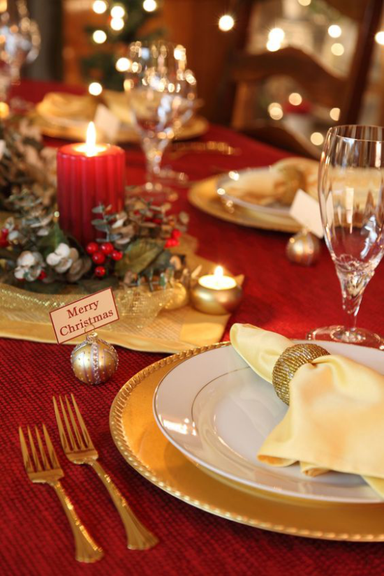 Weihnachtsdeko in Rot und Gold festlich gedeckter Tisch rote Tischdecke edles Porzellan vergoldetes Besteck rote Kerze