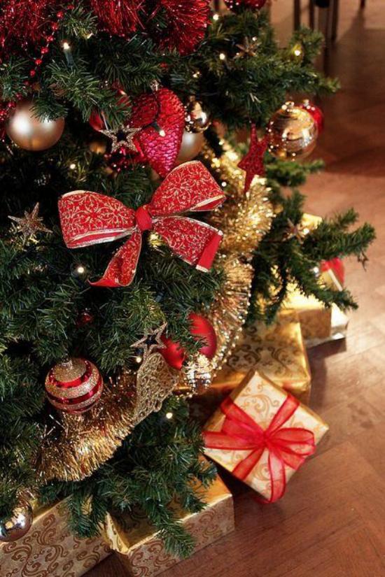 Weihnachtsdeko in Rot und Gold große rote Schleife Kugeln Girlanden zahlreiche Geschenke unter dem Christbaum