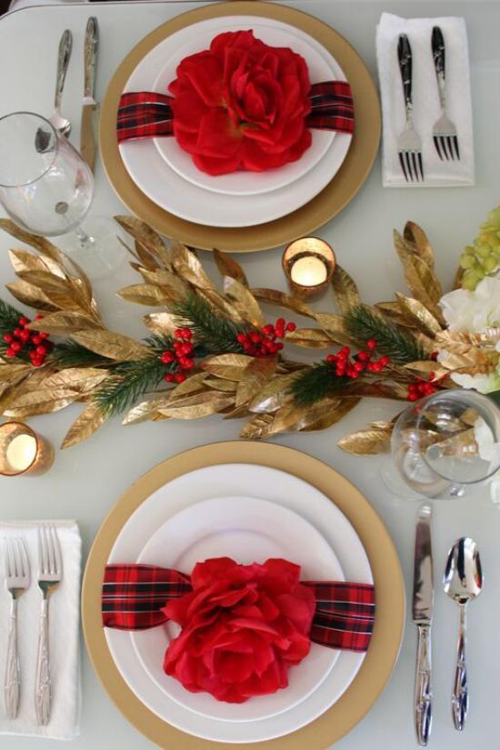 Weihnachtsdeko in Rot und Gold karierte Schleifen rote Blüten schmücken das edle Geschirr Kerzen goldene Akzente Blätter