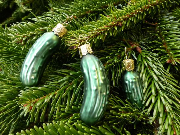 Weihnachtsgurke grüne Glasornamente in Gurkenform zwischen den Tannenzweigen versteckt