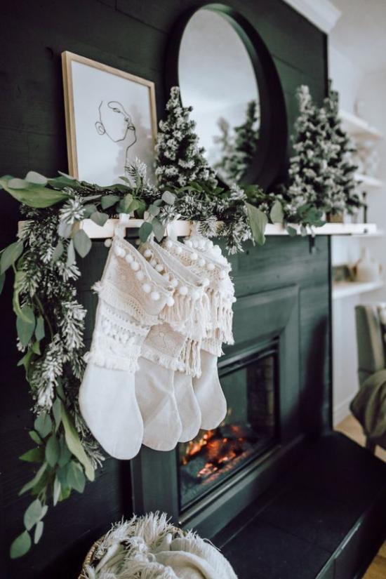 traumhafte Weihnachtsdeko im Wohnzimmer Grüne Girlande weiße Nikolausstiefel am Kaminsims