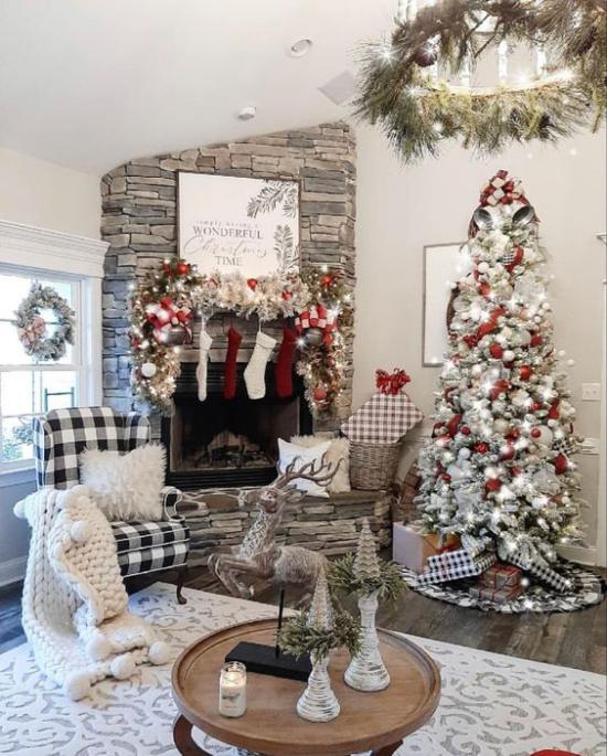 traumhafte Weihnachtsdeko im Wohnzimmer Kamin aus Naturstein hoher Christbaum dekoriert helle Farben dominieren