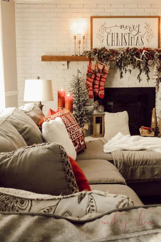 traumhafte Weihnachtsdeko im Wohnzimmer bequeme Couch Kamin Tannengrün rote Stiefel Kerzen