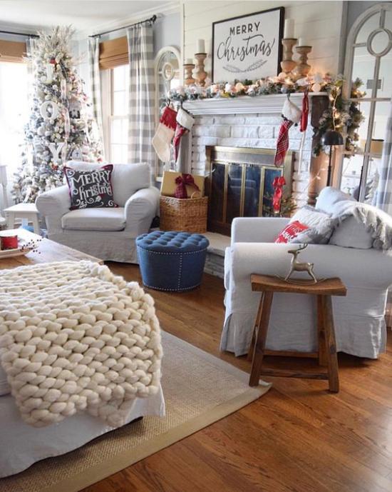 traumhafte Weihnachtsdeko im Wohnzimmer helle Farben dominieren kuschelige Decke Christbaum vor dem Fenster geschmückter Kamin