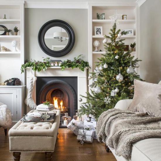 traumhafte Weihnachtsdeko im Wohnzimmer in Beige wenig Schmuck grüner Christbaum Kaminfeuer