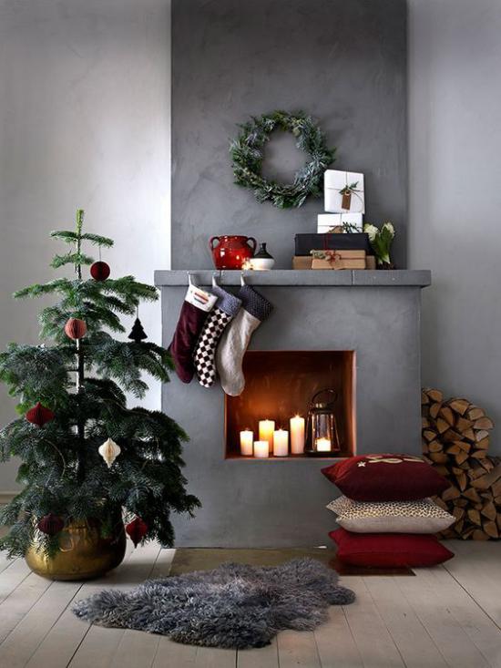traumhafte Weihnachtsdeko im Wohnzimmer kleiner Christbaum Kamin Kerzen grauer Hintergrund Industrial Style