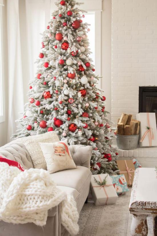 traumhafte Weihnachtsdeko im Wohnzimmer schöne Raumdekoration helle Atmosphäre Christbaum rote Akzente weiche Wurfdecke Kissen ideen