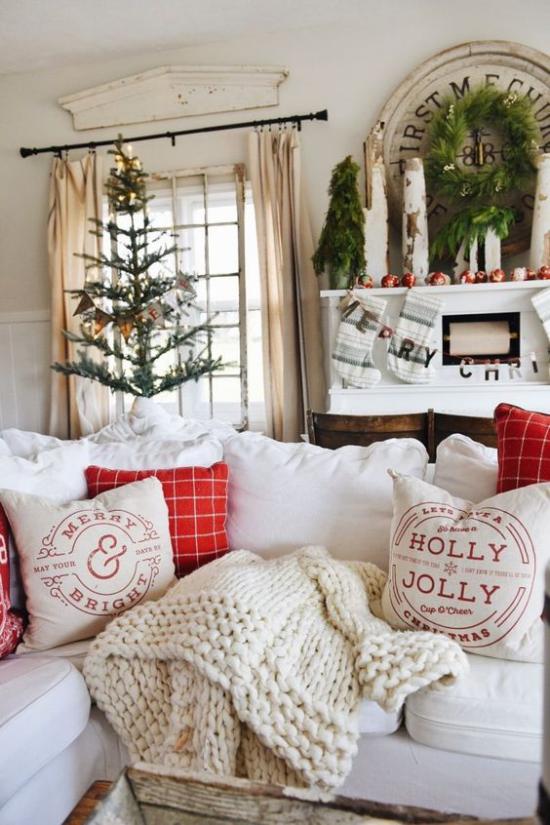 traumhafte Weihnachtsdeko im Wohnzimmer schöne Raumdekoration helle Atmosphäre Christbaum rote Akzente weiche Wurfdecke Kissen