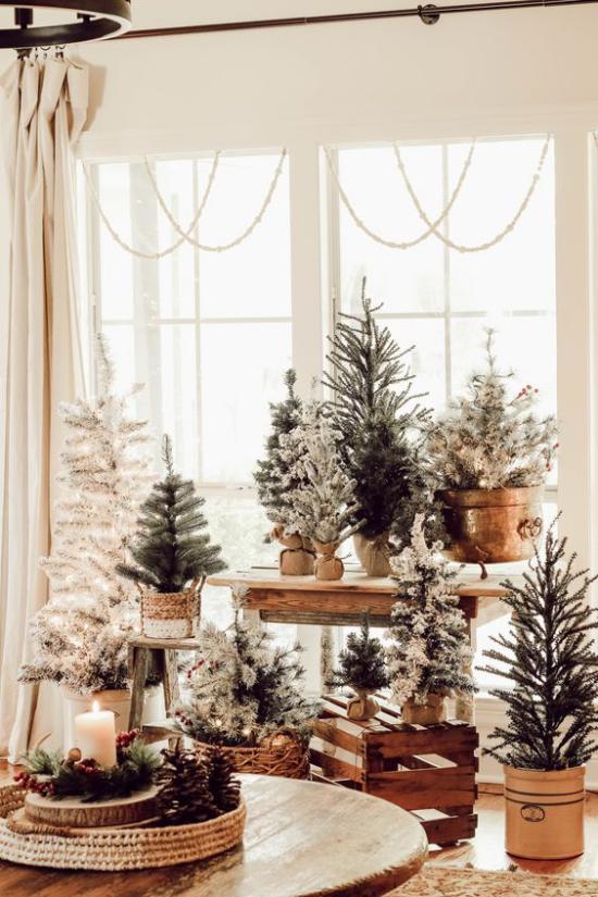 traumhafte Weihnachtsdeko im Wohnzimmer viele kleine Tannenbäume vor dem Fenster arrangiert