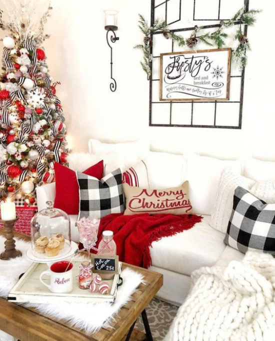 traumhafte Weihnachtsdeko im Wohnzimmer weiße Couch rote Akzente kuschelige Decke Kissen Tannenbaum links