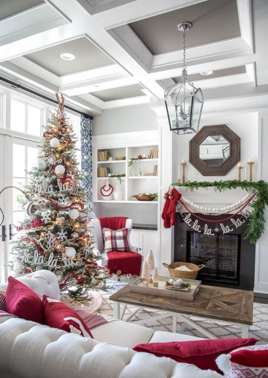 traumhafte Weihnachtsdeko im Wohnzimmer weiße Couch rote Kissen Tannenbaum grüne Girlande am Kamin