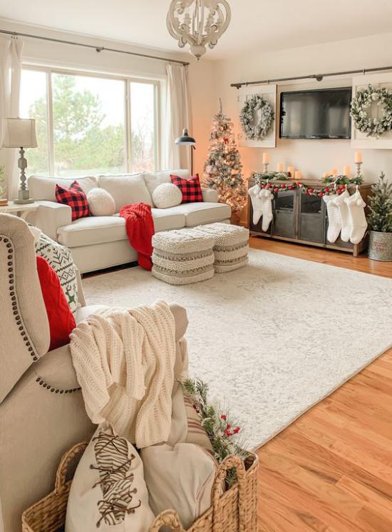 traumhafte Weihnachtsdeko im Wohnzimmer weiter Raum in Weiß und Hellbeige geschmückter Christbaum links rote Akzente