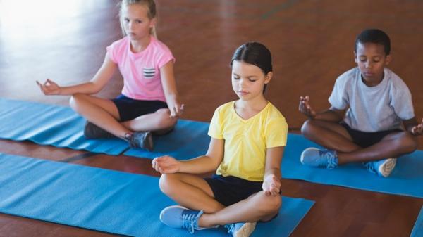 School kids meditating during yoga class