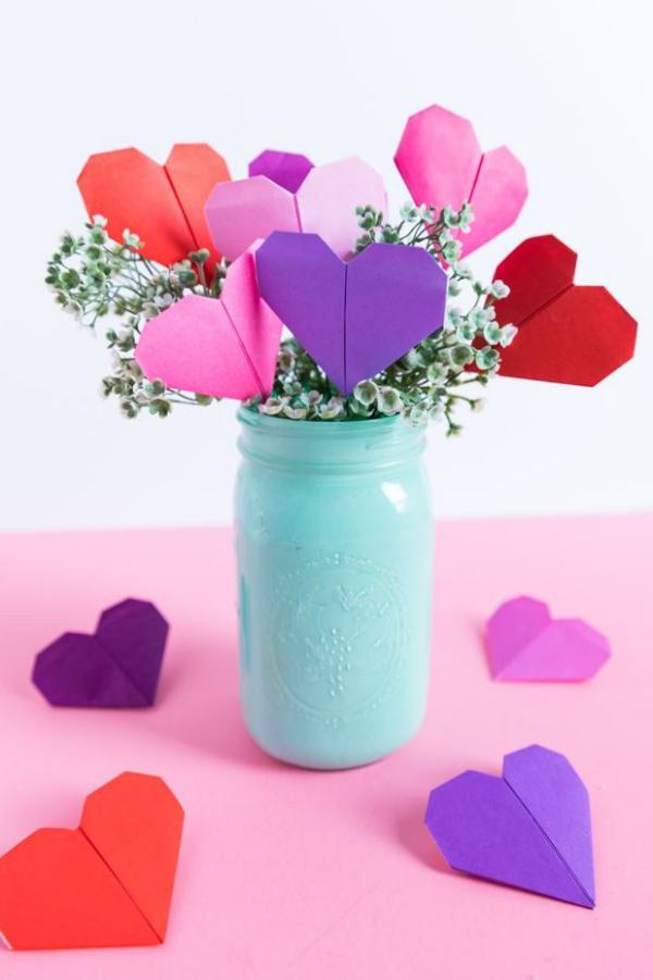 DIY Geschenke zum Valentinstag kleine Origami Herzen aus buntem Papier in einem hellblauen Einweckglas mit Blumen arrangiert