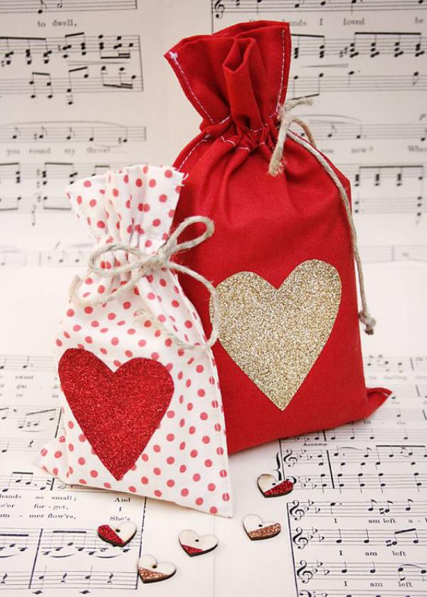 DIY Geschenke zum Valentinstag zwei Geschenktüten aus rotem Stoff mit Herzen dekoriert
