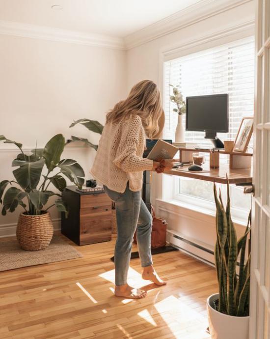 Home Office Guide angenehme Raumatmosphäre Grünpflanzen junge Frau im Stehen arbeiten