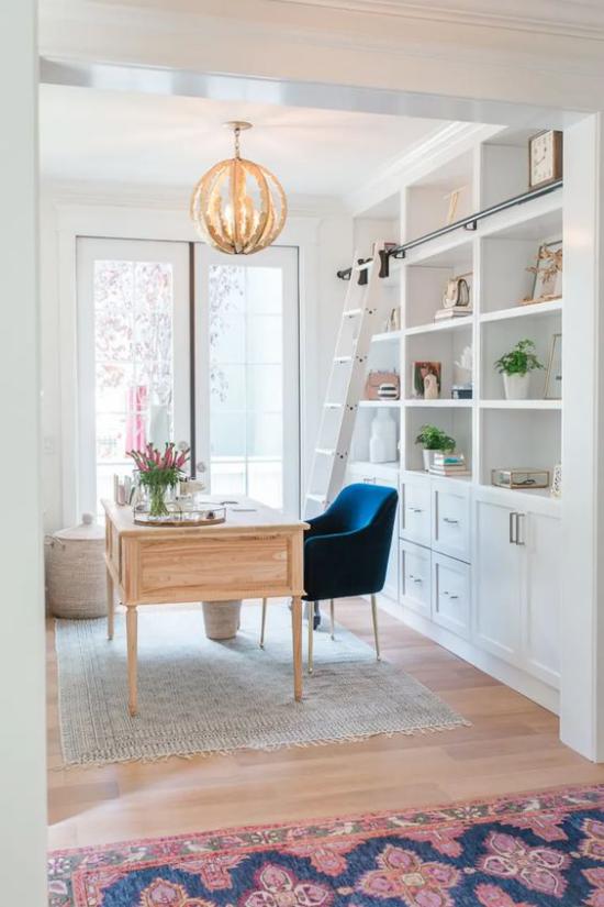 Home Office Guide ansprechende Raumatmosphäre Schrank Holztisch marineblauer Sessel gute Beleuchtung Fenster Hängelampe