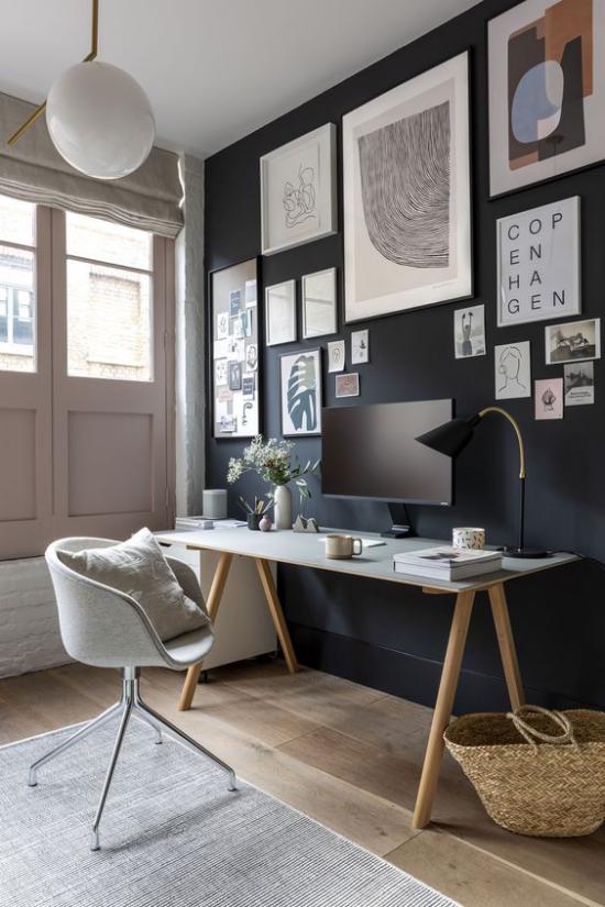 Home Office Guide ansprechende stilvolle Raumgestaltung dunkle Wand über dem Schreibtisch abstrakte Bilder grauer Teppich