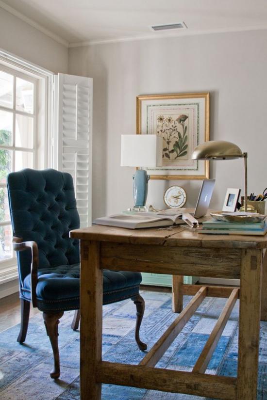 Home Office im Landhausstil Massivholztisch marineblauer Sessel blauer Teppich Lampen Wandbild stilvolle Raumgestaltung